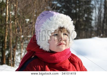 Little Sad Girl Stands In Winter Forest And Looks Into Distance
