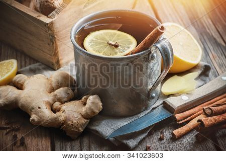 Ginger Tea Cup With Lemon And Cinnamon, Ginger Roots, Knife And Cinnamon Sticks On Kitchen Table.