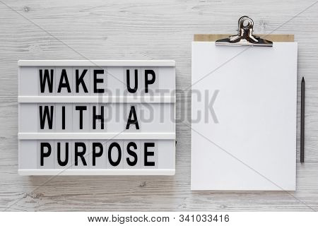'wake Up With A Purpose' Words On A Lightbox, Clipboard With Blank Sheet Of Paper On A White Wooden