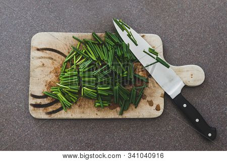 Freshly Cut Chive On Chopping Board With Knife Next To It