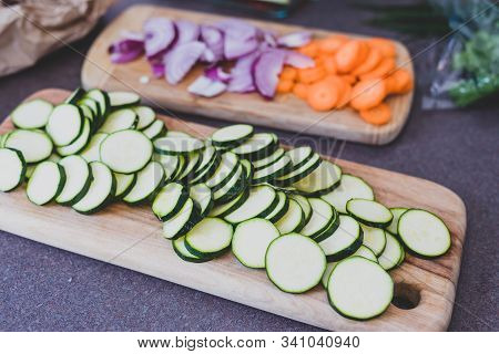Meal Prepping Healthy Plant-based Recipes, Freshly Cut Zucchini Carrots And Onion On Choppng Boards