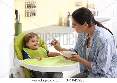 Young Nanny Feeding Cute Little Baby In Kitchen