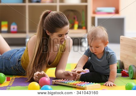 Teen Nanny And Cute Little Baby Playing With Xylophone At Home