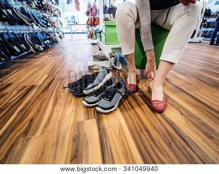 Lyon, France - Sep 8, 2019: Young Woman Measuring Multiple Comfortable Crocs Shoes Inside The Dedica