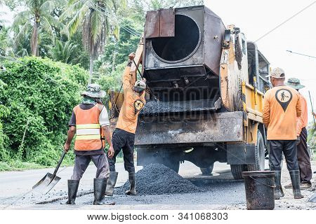 Group Of Workers Working On Repairing Asphalt Road. Workers On A Road Construction, Industry And Tea