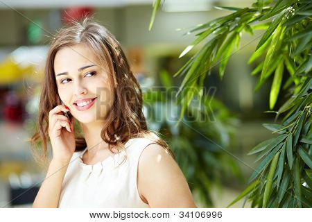 Lovely shopping girl talking on the phone in mall