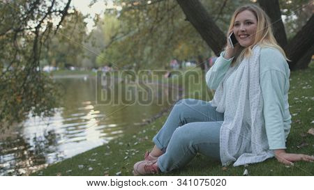 Woman Plus Size Sit On Lake Bank Park Background. Pretty Caucasian Girl Talk Smartphone Summertime City Parkland River Surface. Happy Lady Smile Enjoy Mobile Conversation