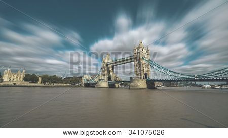 Tower Bridge London Time lapse. Famous monument standing on Thames river in England. Tourist boats sailing along the coast. Soft clouds fast flow in blue sky. Travel recreation concept.