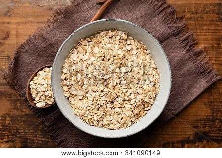 Oats, Rolled Oat Flakes Or Oatmeal In Bowl On Burlap Surface, Wooden Table Background. Top View. Hea