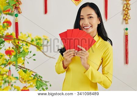 Positive Pretty Young Woman Holding Many Red Envelopes With Money She Is Gifting To Friends And Rela