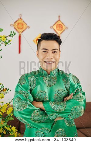 Portrait Of Handsome Young Man Standing In Traditional Costume In Room Decorated For Tet Celebration