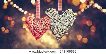 Wicker hearts made of straw, Vintage styled St. Valentine's Day art design. Beautiful Valentine card design. Couple of hanging hearts over brown retro background, love concept. Holiday backdrop