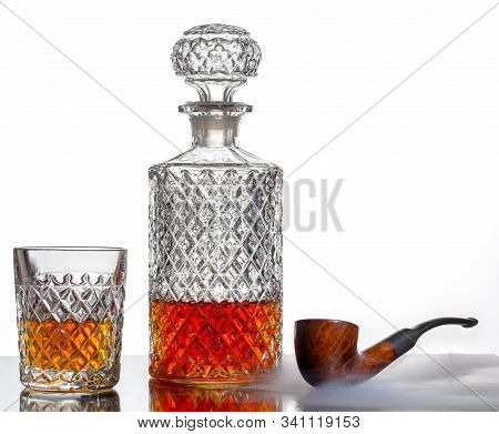 A Cut Glass And A Decanter Of Whisky And A Smoking Pipe On The Table