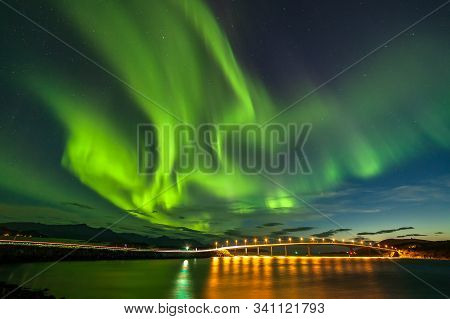 Polar Lights Aurora Borealis, Northern Lights With Many Clouds And Stars In The Sky Over Bridge To S