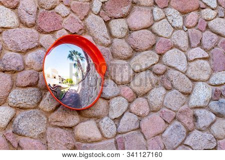 Convex Safety Mirror On Cobblestone Wall With Reflection Of Roadside View. A Classic Stone Wall And