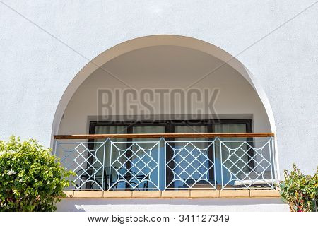 Arch Terrace With Table And Sunbeds. A Semicircular Window At Hotel Balcony. Curtains Drawn Up On Th