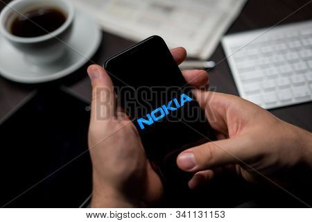 New York, New York / USA - 11 11 2019: Logo of Nokia on the iPhone X in hands in office