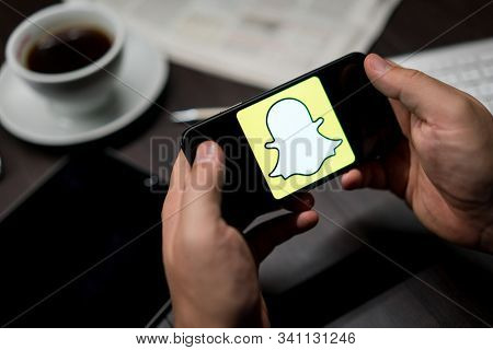 New York, New York / USA - 11 11 2019: Logo of Snapchat on the iPhone X in hands in office