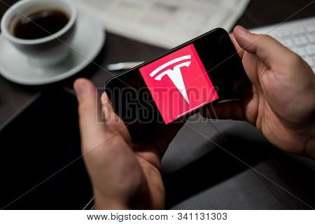 New York, New York / USA - 11 11 2019: Logo of Tesla on the iPhone X in hands in office