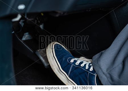Partial View Of Mechanic In Sneakers Pressing Brake Pedal In Car