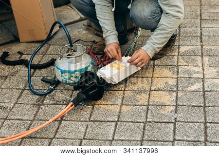 A Plumber Or Utility Worker Repairs A Broken Water Pump On The Street. The Work Of Municipal Utiliti