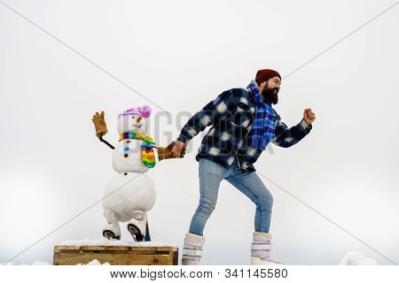 Man In Winter Clothes. Bearded Man Runs With Snowman. Sportsman Running With Snowman In Winter Hat.