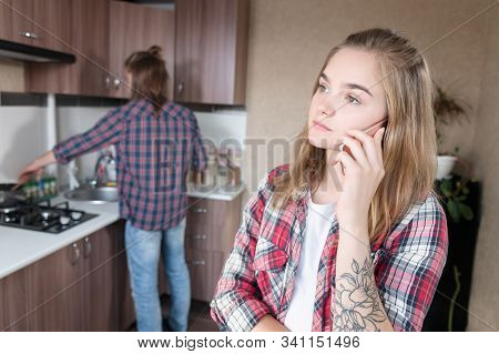 A Young Girl Is Talking On A Cell Phone In The Kitchen Amid Her Husband Or Boyfriend Washing Dishes.