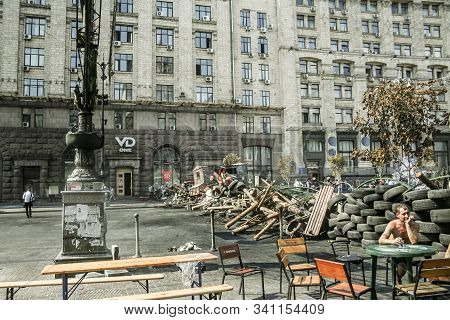 Kiev, Ukraine - August 8, 2014: Euromaidan Protester Sitting At A Cafe In Front Of A Huge Barricade