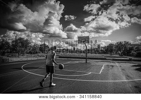 Basketball Player Dribbling In A Playground On A Cloudy Day. Black And White Effect