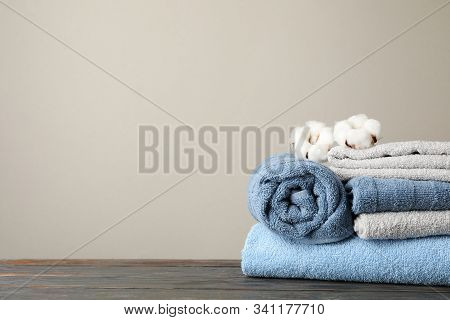 Folded Towels And Cotton On Wooden Table Against Grey Background, Space For Text