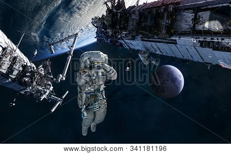 Astronaut, Iss In Orbit Of Earth. Moon. Solar System. Science Fiction. Elements Of This Image Furnis