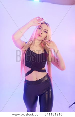Beautiful Woman In Black Leather Pants On A Pink Background