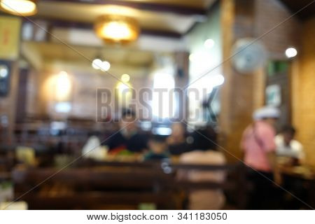Blurred Image Of Group Of People Of Enjoy Talking And Eating Some Food With Their Family On Table In