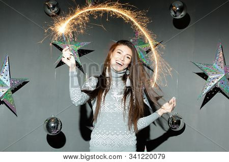 Beautiful Young Woman With Sparkler On Holiday Against The Background Of Silver Stars