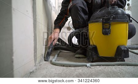 A Worker Vacuums A Concrete Floor. Worker Washes The Floor With A Vacuum Cleaner From Industrial Con