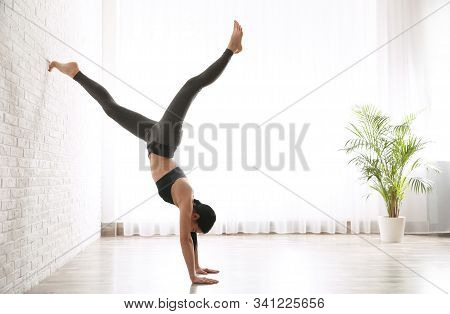 Young Woman Practicing Downward Facing Tree Asana In Yoga Studio. Adho Mukha Vrksasana Pose