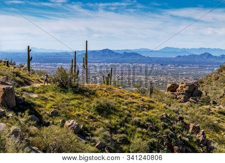 Hiker On Pinnacle Peak Desert Trail In Scottsdale With The Valley Of The Sun In Background.