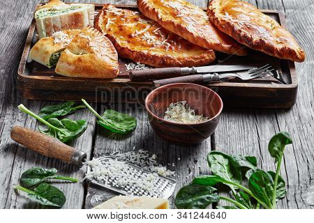 Close-up Of Freshly Baked Calzones, Closed Pizzas With Spinach And Cheese Filling Sprinkled With Gra