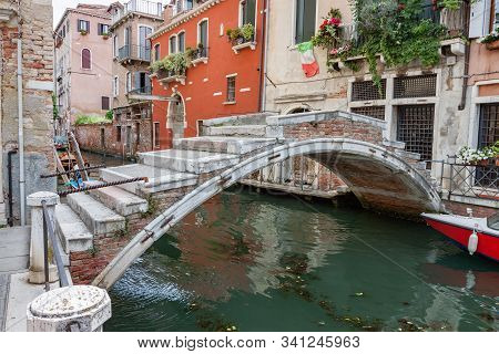 Arched Brick Bridge Over Canal In Venice