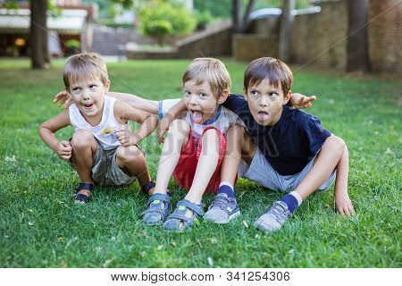 Three Young Boys Making Weird Grimace Faces In Summer Park. Friends Or Siblings Having Fun Outdoors.
