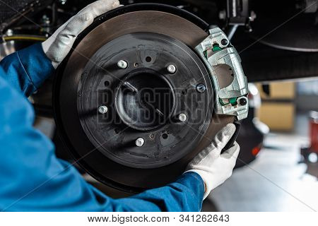 Cropped View Of Mechanic Adjusting Assembled Disc Brakes With Brake Caliper