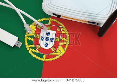 Portugal flag depicted on table with internet rj45 cable, wireless usb wifi adapter and router. Internet connection concept poster