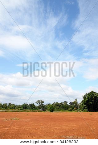 Landscape Of Bare Earth And Tree With A Beautiful Blue Sky Above