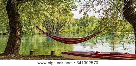 Wide Scenery Of Hammock By The Lake Between Weeping Willow Trees In The Italian Nature Reserve Posta