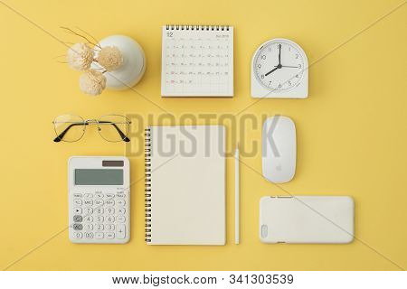 Notebook, Mouse, Phone, Calculator, Glasses, Pen, Calendar, Alarm On Yellow Background. Flatlay, Top
