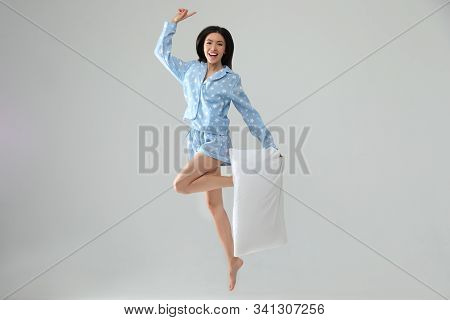 Beautiful Asian Woman With Pillow Jumping On Light Grey Background. Bedtime