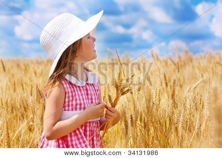 Hermosa chica de preescolar en el campo de trigo