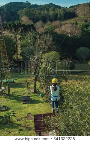 Bento Goncalves, Brazil - July 11, 2019. Girl Descending By Cable In A Zip-line Over Meadows And Tre