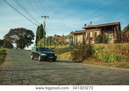 Bento Goncalves, Brazil - July 13, 2019. Car Passing By A Stone Paved Road Next To A Charming Wood H