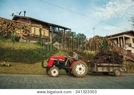 Bento Goncalves, Brazil - July 13, 2019. Tractor Pulling Cart With Brushwood On A Stone Paved Road,